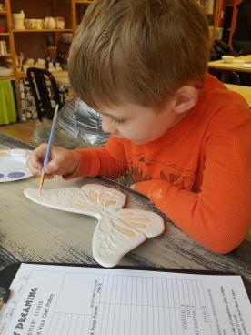 Connor paints Pottery