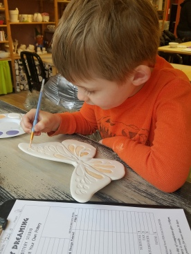 Connor paints Pottery